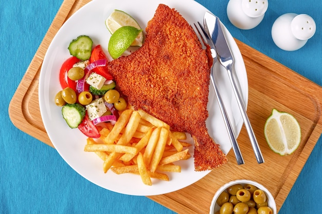 Crispy fried flounder in breadcrumbs served with fresh vegetables, feta, olives greek salad and french fries on a white plate with silver fork and knife on a cutting board, view from above