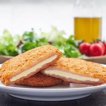 Хрустящие жареные блюда с куриным сыром и ветчиной салат сан-хакобо в сопровождении