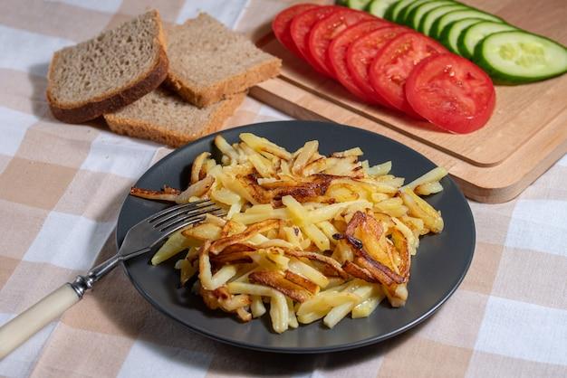 Хрустящий жареный картофель с хлебом и нарезанными овощами