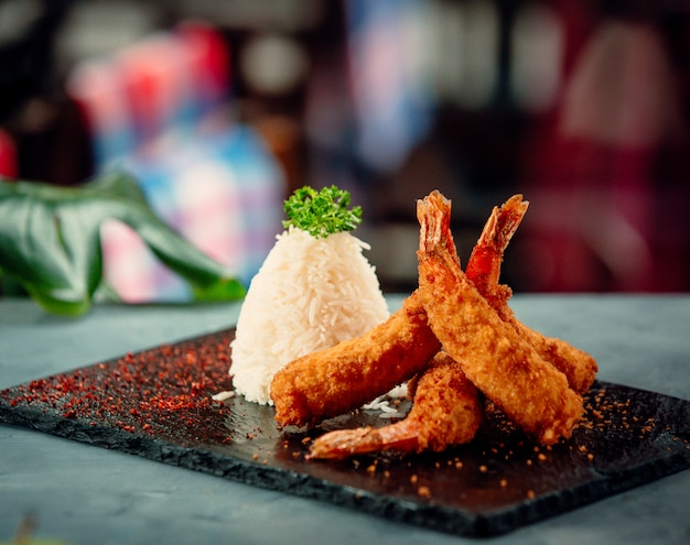 Crispy fried shrimps with rice on black stone board