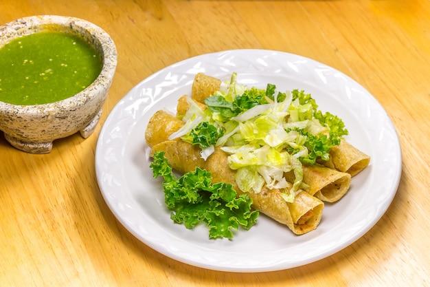 Хрустящие тако на белом блюде с зеленым соусом