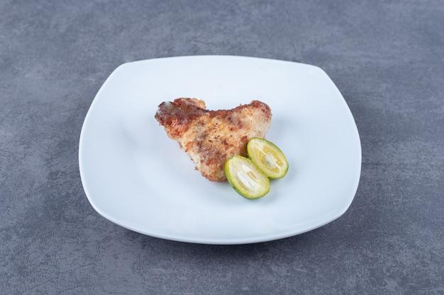 Ala fritta croccante sul piatto bianco.