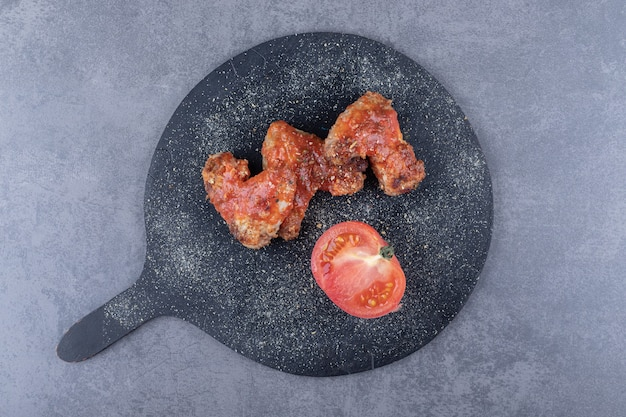 블랙 보드에 바삭하게 튀긴 날개와 토마토.