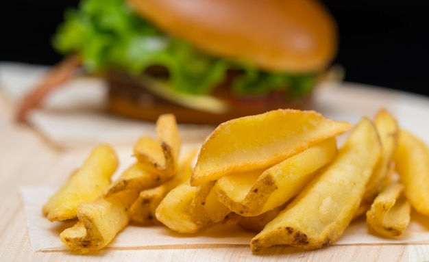 Crispy golden deep fried potato chips or french fries served with a burger on a wooden board, close up view