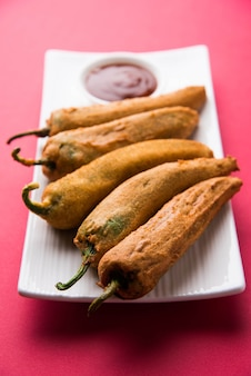 Хрустящий зеленый перец чили пакора или мирчи баджи, подается с томатным кетчупом на мрачном фоне. это популярная закуска к чаепитию из индии, особенно в сезон дождей. выборочный фокус