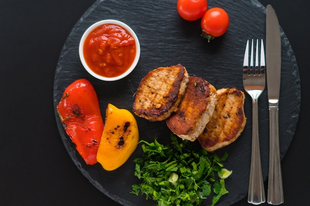 Crispy grilled medallions of pork fillet served with roast peppers, greens and tomato sauce viewed top down