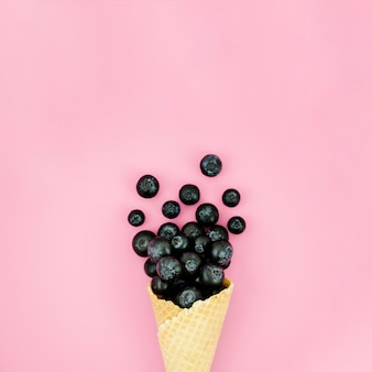 Crispy ice cream cone with blueberry on light surface