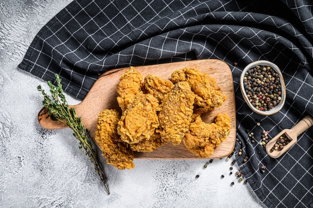 Хрустящая жареная курица по-кентукски с картофелем фри и помидорами.