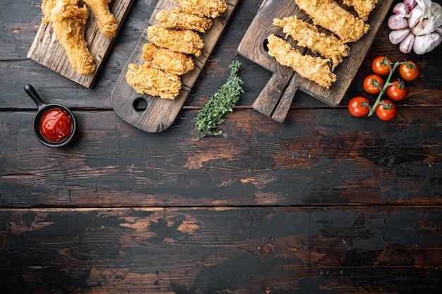 古い暗い木製のテーブルにカリカリのケンタッキーフライドチキンミート