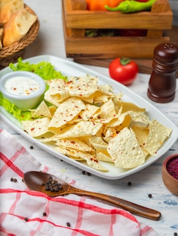 Crispy lavash chips with herbs and sour cream mayonnaise sauce.