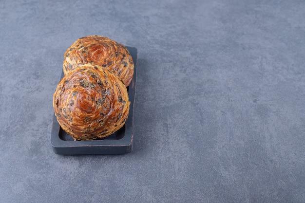 Хрустящий слоистый шоколадный гогаль на деревянной тарелке, на мраморе.