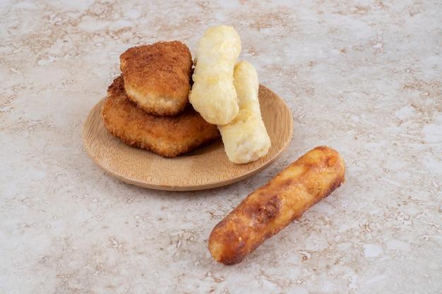 Хрустящие наггетсы, сырные палочки и сосиски гриль на деревянном блюде.