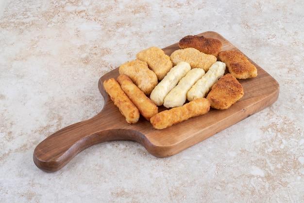 Pepite croccanti, bastoncini di formaggio e salsicce alla griglia su un piatto di legno.
