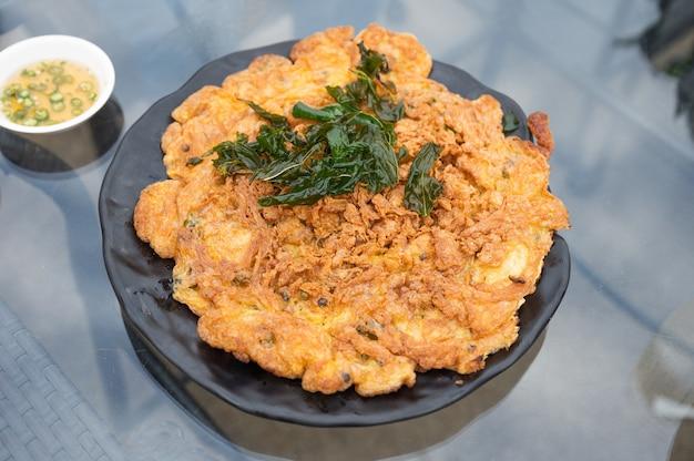 テーブルの上の黒いプレートに豚肉とバジルの葉を刻んだサクサクのオムレツ