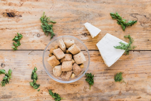 Crispy pastries with cheese blocks and parsley on wooden table