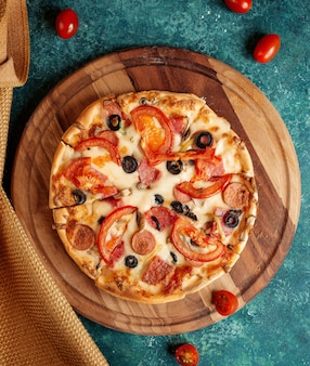 Crispy pizza with tomatoes and olives and sausages