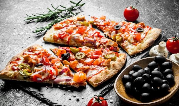 토마토, 로즈마리, 올리브를 곁들인 바삭한 피자. 어두운 소박한 배경에