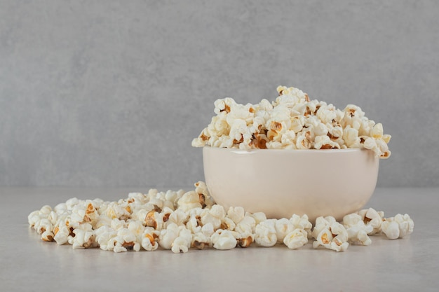 Crispy popcorn inside and around a white bowl on marble surface.