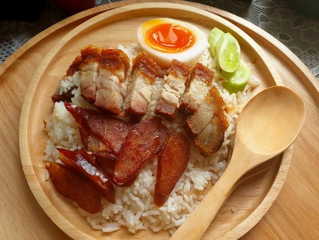 바삭한 삼겹살 중국 소시지와 삶은 달걀을 밥 위에 얇게 썬 오이
