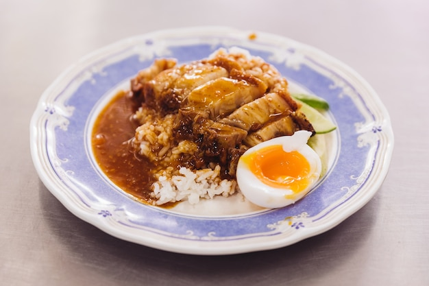 Crispy pork belly with rice pouring with gravy served with half of boiled egg.