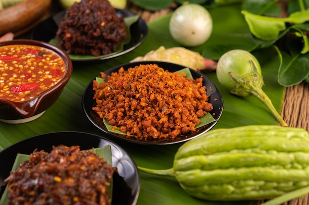 Crispy pork chili paste on banana leaves in a plate with side dishes.