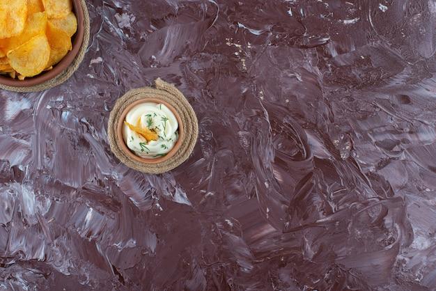 サクサクのポテトチップスとヨーグルトをトリベットのプレートに、大理石のテーブルに。
