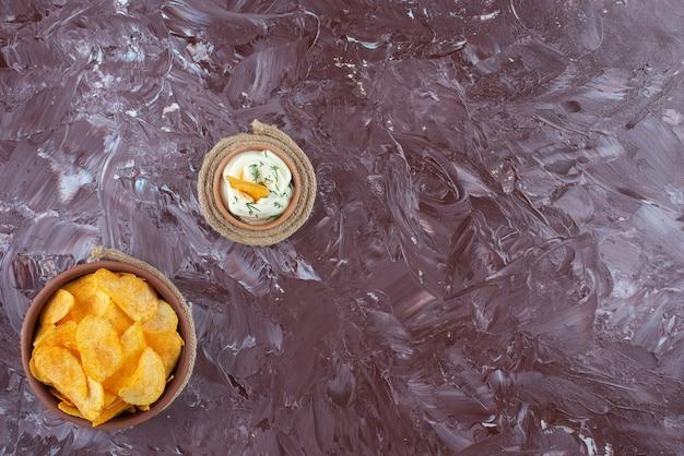 대리석 테이블에 있는 삼각 접시에 있는 바삭한 감자 칩과 요구르트.