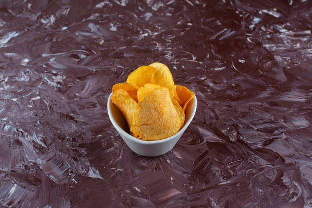 Crispy potato chips in a bowl, on the marble table.