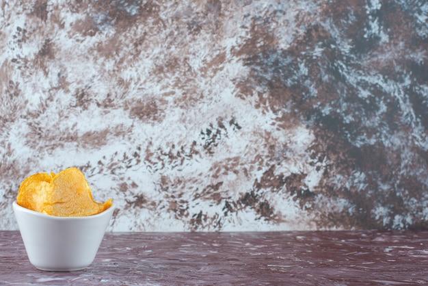 Patatine croccanti in una ciotola, sul tavolo di marmo.