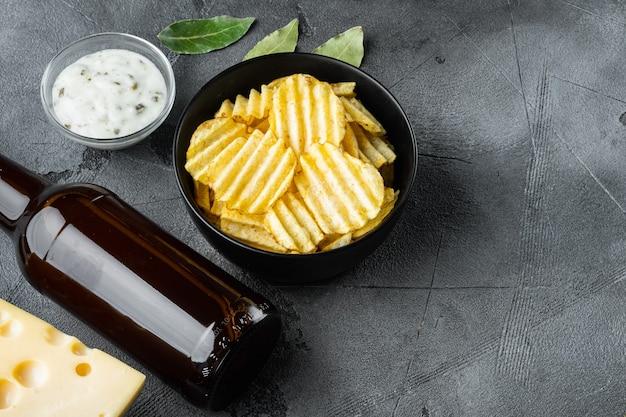 바삭한 감자 칩. 회색 돌 테이블에 치즈와 양파를 곁들인 바다 소금으로 구운 감자 조각, 디핑 소스, 맥주 병