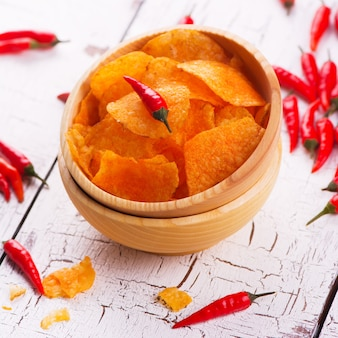 Crispy potato chips with paprika in a wooden bowl on white wooden background