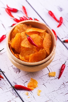 Crispy potato chips with paprika in a wooden bowl on white wooden background.