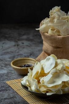 Crispy potato chips with tomato sauce snack concept.