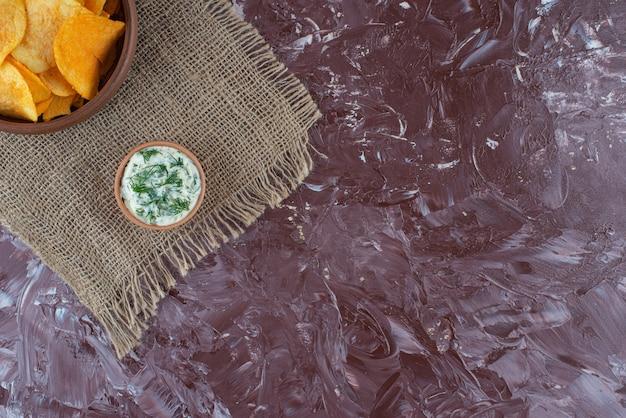 Patatine fritte e yogurt croccanti in piatti su struttura, sulla tavola di marmo.