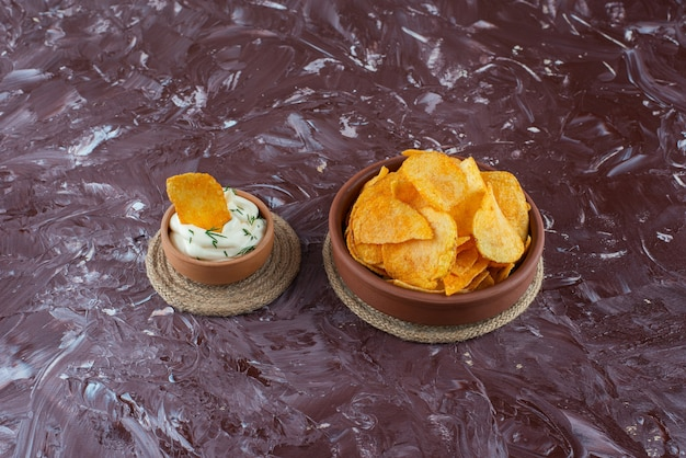 Patatine croccanti e yogurt in piatti su sottopentola, sul tavolo di marmo.