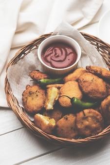 サクサクのポテトパコラまたはアルーパコダまたはバタタバジにトマトケチャップ、唐辛子と唐辛子のグリーンフライ、人気のインド料理のオールタイムスナック、セレクティブフォーカス