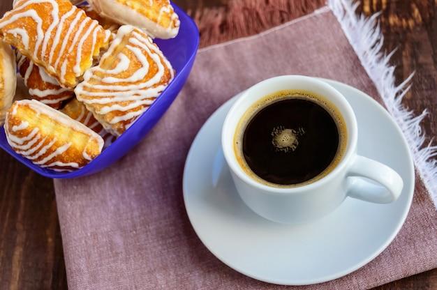 木製のテーブルにホワイトチョコレートとブラックコーヒーカップとシャキッとしたパフクッキー