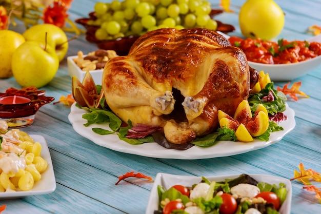 お祝いの感謝祭のテーブルにサラダとクリスピーローストチキン。