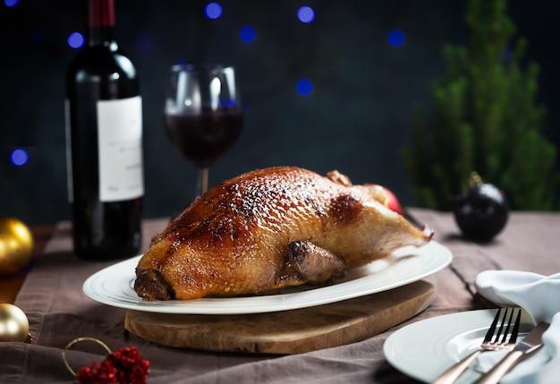 Хрустящая жареная утка на белой тарелке, готовая к сервировке, фотография в темном и капризном стиле