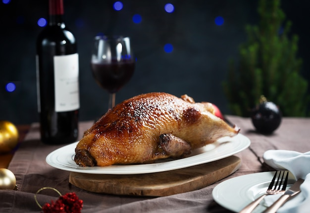 Crispy roasted duck on a white plate ready for serving, dark and moody style photo