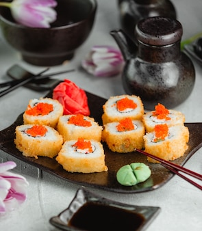 Crispy rolls with red caviar,ginger and wasabi on a black plate.