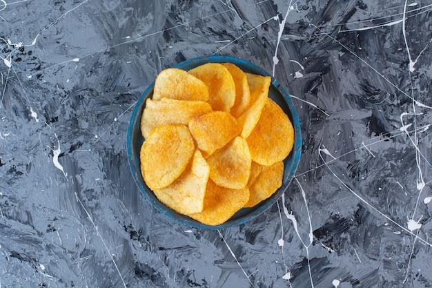 Хрустящие, острые картофельные чипсы на деревянной тарелке на мраморной поверхности
