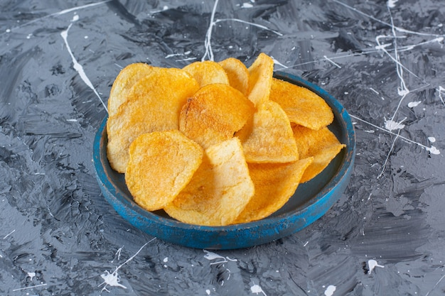 Crispy, spicy potato chips in wooden plate, on the marble surface