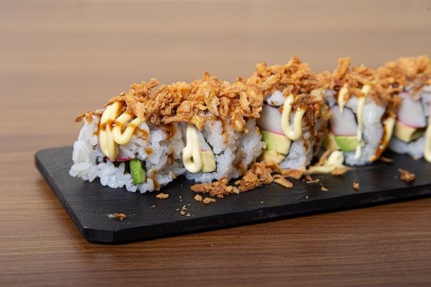 玉ねぎの炒め物、アボカド、カニのカリカリ巻き寿司。寿司メニュー。日本食。