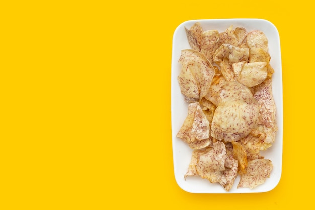黄色の背景に白いプレートのサトイモチップ。