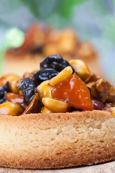 Хрустящая тарталетка с начинкой, в тарталетках из тестовых орехов и сухофруктов, покрытых карамелью, небольшой аналог торта с разнообразными начинками