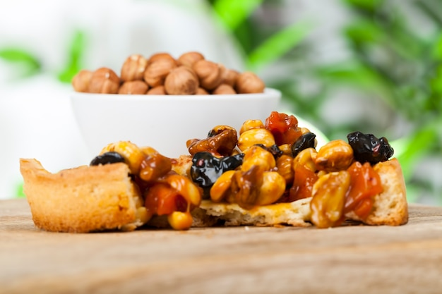 Хрустящая тарталетка с фундуком, арахисом и другими ингредиентами, тарталетка из пшеничного теста с орехами и сухофруктами в крем-карамели, пшеничная тарталетка со сладкой начинкой