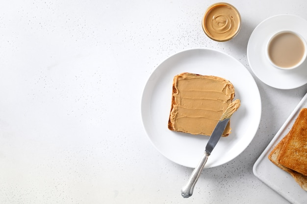 Crispy toast with peanut paste for healthy breakfast on white background. view from above. copy space.