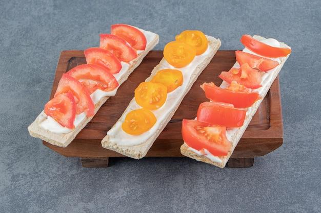 Toast croccanti con pomodori su tavola di legno.