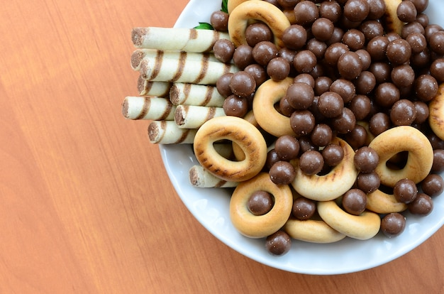Crispy tubules, chocolate melting balls and bagels lie in a white plate on a wooden table.